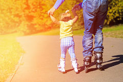 Father teaching little daugther to roller skate in Royalty Free Stock Photography