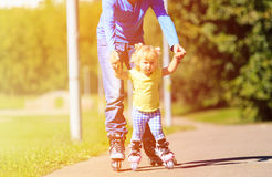 Father teaching little daugther to roller skate in Stock Photo
