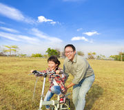 Father teaching little girl to ride bicycle. Happy Father teaching little girl to ride bicycle stock image