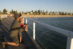 Father teaching little young son to be a fisherman, fishing together on sea dock embankment enjoying and learning using the fish r stock photos