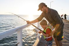 Father teaching little young son to be a fisherman, fishing together on sea dock embankment enjoying and learning using the fish r stock photography