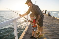 Father teaching little young son to be a fisherman, fishing together on sea dock embankment enjoying and learning using the fish r stock image