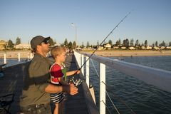 Father teaching little young son to be a fisherman, fishing together on sea dock embankment enjoying and learning using the fish r stock photo