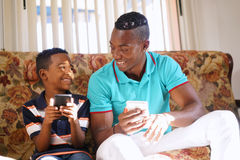 Father Teaching Mobile Telephone Technology To Boy At Home. Happy black family at home. African american father and child playing game with cell phone. Hispanic Stock Photography