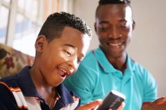 Father Teaching Mobile Telephone Technology To Son At Home. Happy black family at home. African american father and child playing game with cell phone. Hispanic Royalty Free Stock Photos