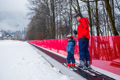 Father teaching skiing his happy little son in Kitzbuehel, Austria Royalty Free Stock Photography