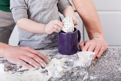 Father teaching son baking cookies Royalty Free Stock Photography