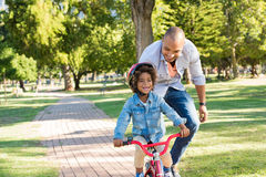 Father teaching son cycling. Lovely father teaching son riding bike at park. Happy father helping excited son to ride a bicycle in a summer day. Young smiling royalty free stock photo