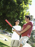 Father teaching son (10-12) how to hold baseball bat, standing on grass in park, smiling (tilt) Royalty Free Stock Photo