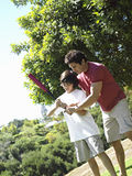 Father teaching son (10-12) how to hold baseball bat, standing on grass in park (tilt) Royalty Free Stock Photos