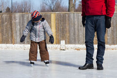 Father teaching son how to ice skate Stock Image