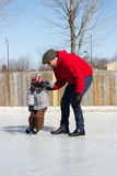 Father teaching son how to ice skate Royalty Free Stock Images
