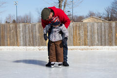Father teaching son how to ice skate Royalty Free Stock Image