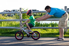 Father teaching son how to ride a bicycle stock images