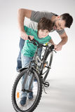 Father teaching son how to ride bicycle on white Stock Photography