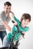 Father teaching son how to ride bicycle on white Royalty Free Stock Photos