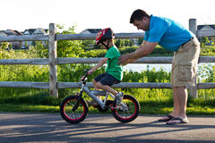 Father teaching son how to ride a bike Stock Image
