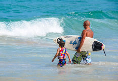 Father teaching son how to surfing. royalty free stock photos