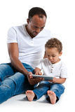Father teaching son how to use a new tablet PC. Learning and early education concept royalty free stock photography