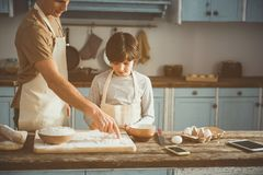 Father teaching son making cakes. Dad pointing at processing board with flour. Boy holding egg and looking with interest. Copy space in right side Stock Photo
