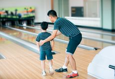 Father teaching son for play bowling at bowling club royalty free stock photo