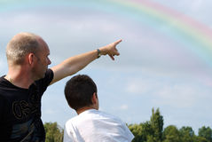 Father teaching son about rainbows. A father and his son. The father is pointing to the rainbow, teaching his son about nature Royalty Free Stock Images