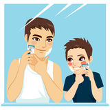 Father Teaching Son Shaving. And having fun together on bathroom mirror Royalty Free Stock Images