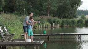 Father teaching son to cast fishing rod on lake stock video footage