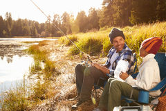 Father Teaching Son To Fish By Lake Royalty Free Stock Photos