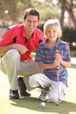 Father Teaching Son To Play Golf Stock Image
