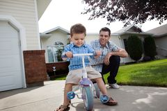 Free Father Teaching Son To Ride A Tricycle Royalty Free Stock Photography - 22345607
