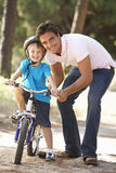 Father Teaching Son To Ride Bicycle Stock Photo