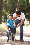 Father Teaching Son To Ride Bicycle Royalty Free Stock Photos