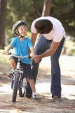 Father Teaching Son To Ride Bicycle Stock Images