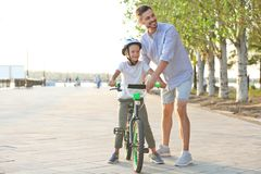 Father teaching son to ride bicycle royalty free stock images