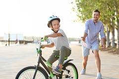 Father teaching son to ride bicycle stock photography
