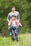 Father Teaching Son To Ride Bike In Countryside. Smiling Stock Photo
