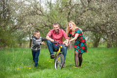 Father teaching son to ride a bike by his example Stock Photos