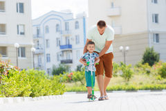 Father teaching son to ride a scooter royalty free stock photography