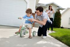 Father Teaching Son To Ride Tricycle. Father teaching his son to ride tricycle while wife standing in background stock photos