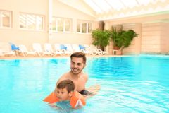 Father teaching son to swim with inflatable sleeve royalty free stock photos
