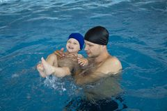 Father teaching son to swim in swimmimg pool. Having fun with daddy stock image