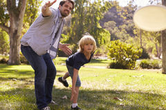 Father Teaching Son To Throw Frisbee In Park Royalty Free Stock Photos