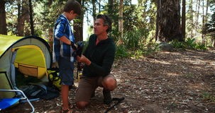 Father teaching son to use trekking pole outside tent. At campsite stock footage