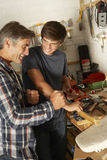 Father Teaching Son To Use Workbench In Garage Stock Photography