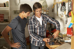 Father Teaching Son To Use Workbench In Garage Stock Photo