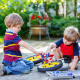 Father teaching two little kid boys to repair chain on bikes. Two little boy friends, twins, learning to repair a bike and to to change a wheel. Siblings working Stock Photos