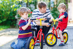 Father teaching two little kid boys to repair chain on bikes Royalty Free Stock Image
