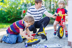 Father teaching two little kid boys to repair chain on bikes. Showing to change a wheel. Family working together outdoors, on warm sunny day. Active leisure stock image