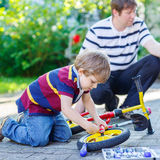 Father teaching two little kid boys to repair chain on bikes. Showing to change a wheel. Family working together outdoors, on warm sunny day. Active leisure Stock Photos